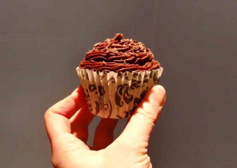 One chocolate cup cake being held up